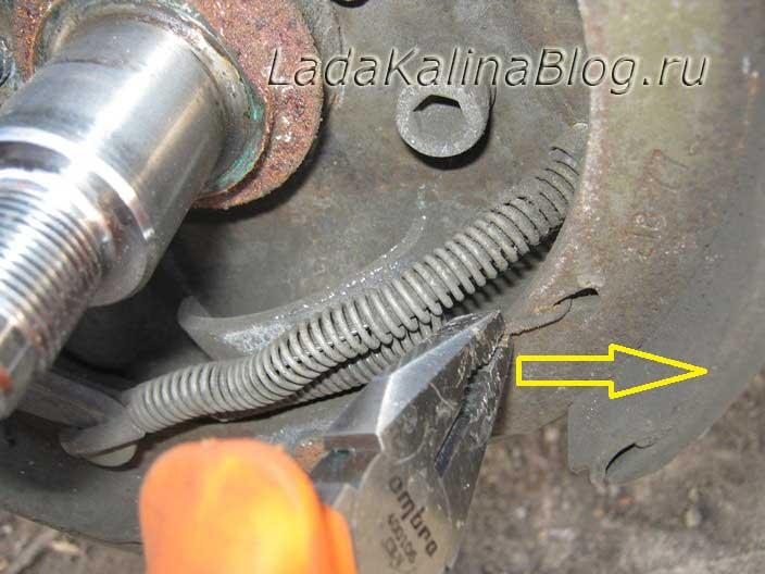 отсоединяем пружину стяжки задних тормозных колодок